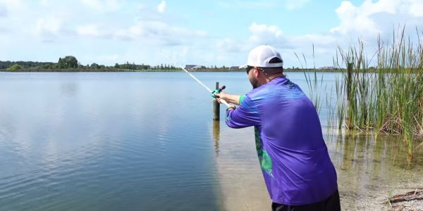man casting bait caster and following through